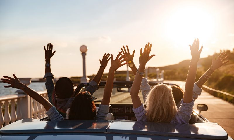 Back view of happy young friends driving cabriolet with raised hands on sunset